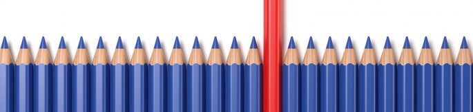 Row of blue penicls with one red pencil sticking up